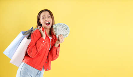 Emotional young woman with money and shopping bags on yellow background. Space for text