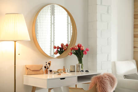 Stylish room interior with dressing table and mirror
