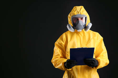 Man in chemical protective suit holding clipboard on black background, space for text. Virus research