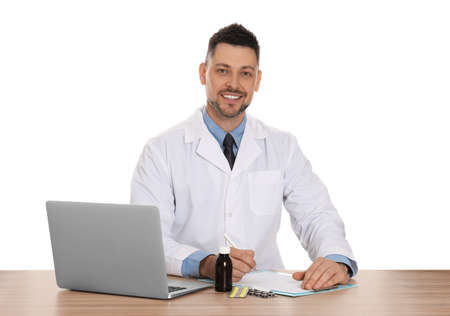 Professional pharmacist working at table against white background