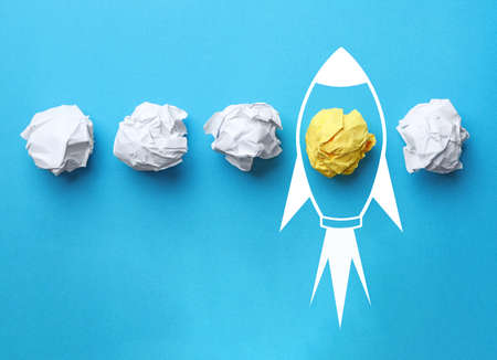 Business startup concept. Colorful crumpled papers and drawn rocket on light blue background, flat lay Stock fotó