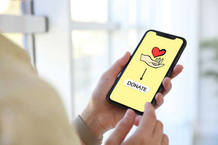 Donations concept. Woman with smartphone indoors, closeup