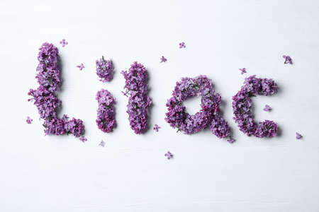 Word LILAC made with beautiful purple flowers on white wooden background, flat lay