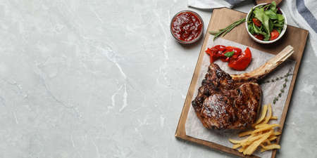 Flat lay composition with delicious grilled ribeye steak on light grey marble table, space for text. Banner design