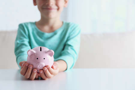 Little boy with piggy bank at white table indoors, closeup. Space for text
