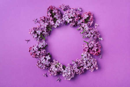 Frame made with beautiful lilac blossom on purple background, flat lay. Space for text