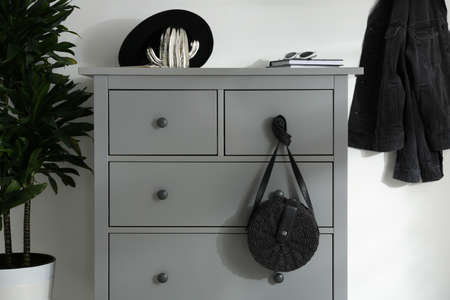 Grey chest of drawers in stylish room. Interior design