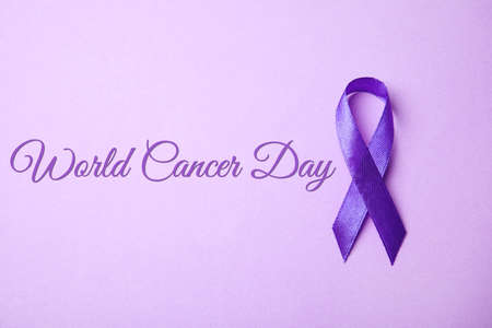 Purple ribbon on lilac background, top view. World Cancer Day