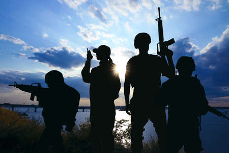 Silhouettes of soldiers with assault rifles and portable radio transmitter patrolling outdoors. Military service
