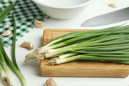 Fresh green spring onions and garlic cloves on white wooden table