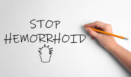 Woman writing phrase STOP HEMORRHOID on white background, top view Banco de Imagens