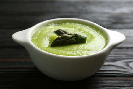 Delicious asparagus soup in bowl on black wooden table Zdjęcie Seryjne