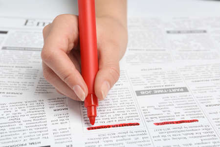Woman marking advertisement in newspaper, closeup. Job search concept