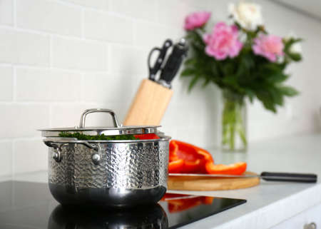 Saucepot with products on induction stove in kitchen