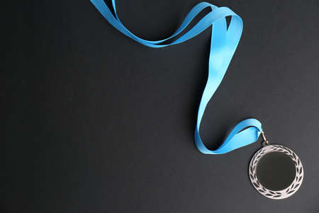 Silver medal on black background, top view. Space for design