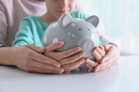 Mother and son with piggy bank at white table indoors, closeup