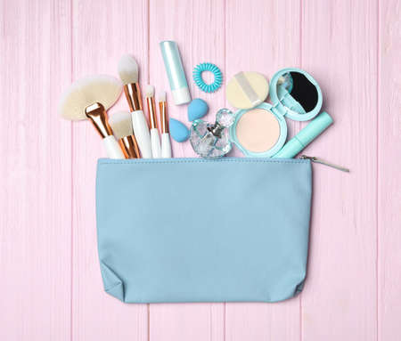 Cosmetic bag with makeup products and beauty accessories on pink wooden background, flat lay