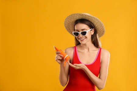 Young woman applying sun protection cream on orange background. Space for text