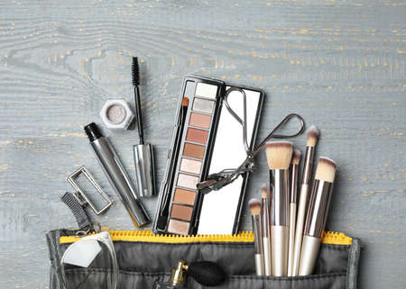 Cosmetic bag with makeup products and beauty accessories on wooden background, flat lay Banque d'images