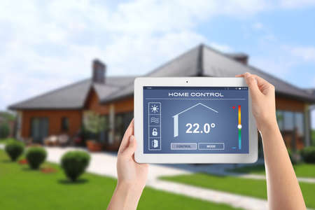 Energy efficiency home control system. Woman using tablet to set indoor temperature, closeup