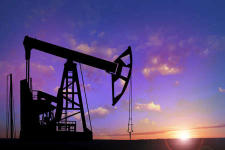 Silhouette of crude oil pump at sunset