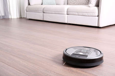 vacuuming floor with modern robotic vacuum cleaner indoors. Space for text