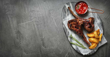 Plate with delicious grilled ribs and space for text on grey table, top view. Banner design