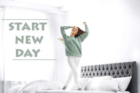 Young woman jumping on bed at home. Start new day