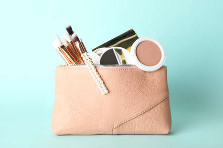 Cosmetic bag with makeup products and beauty accessories on light blue background