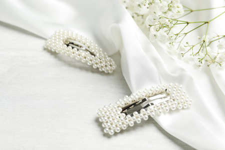 Beautiful hair clips and flowers on white table