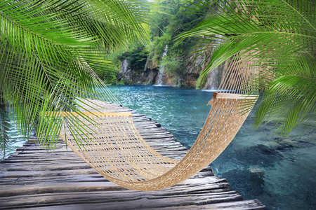 Hammock near wooden bridge and waterfall on sunny day
