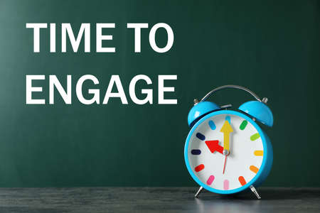 Text Time to engage on green chalkboard near alarm clock