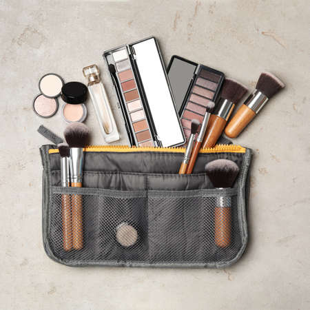 Cosmetic bag with makeup products on light grey stone background, flat lay