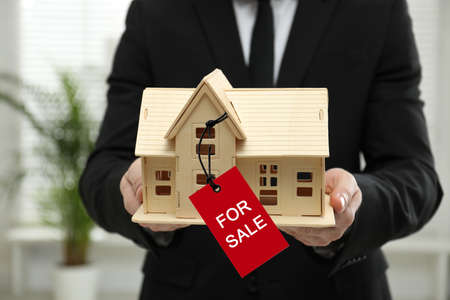 Real estate agent holding wooden house model with SALE label indoors, closeup