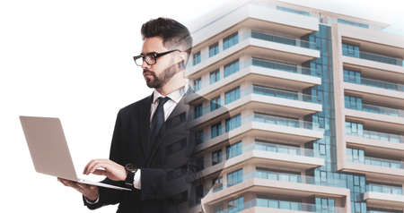 Double exposure of architect working with laptop and building