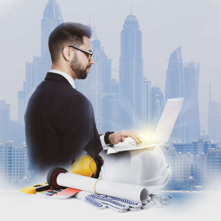 Multiple exposure of architect working with laptop and buildings Archivio Fotografico