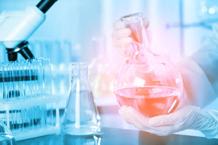 Scientist holding Florence flask with liquid at table, closeup. Laboratory analysis