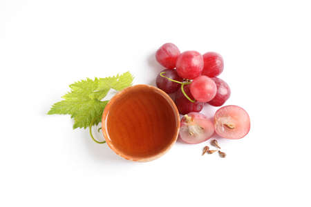 Organic red grapes, seeds and bowl of natural essential oil on white background, flat lay