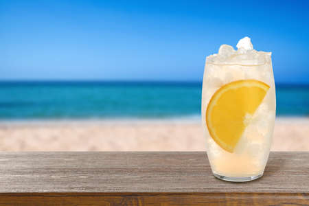 Lemonade with ice cubes and orange slice on wooden table at beach, space for text