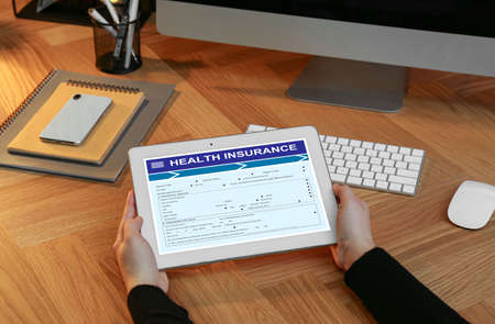 Woman with modern tablet indoors, closeup. Health insurance