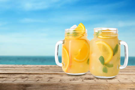 Mason jars with lemonade on wooden table near sea, space for text