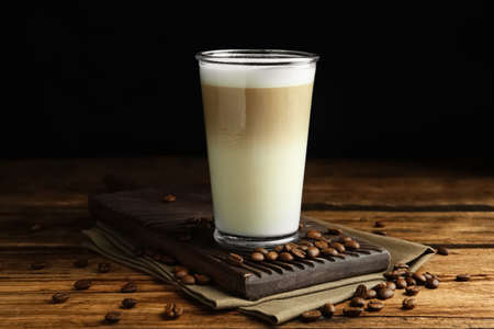 Delicious latte macchiato and coffee beans on wooden table