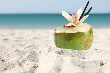 Green coconut with refreshing drink on sandy beach