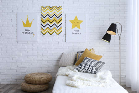 Child's room interior with bed and cute posters on wall Archivio Fotografico