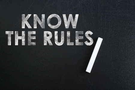 Phrase Know the rules and piece of chalk on blackboard, top view Stock fotó