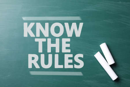 Phrase Know the rules and pieces of chalk on greenboard, top view