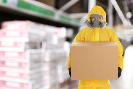 Man wearing chemical protective suit with cardboard box in store. Wholesale market