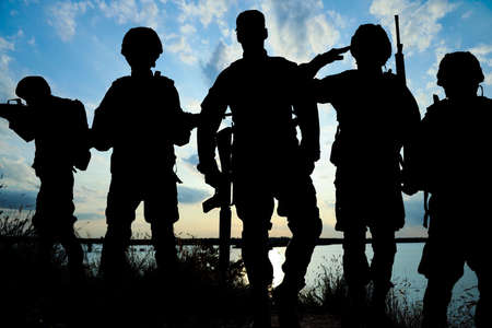 Silhouettes of soldiers with assault rifles patrolling outdoors. Military service