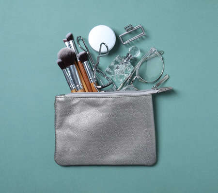 Cosmetic bag with makeup products and beauty accessories on blue-gray background, flat lay Archivio Fotografico