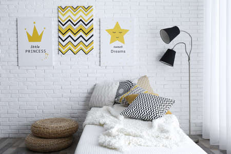 Child's room interior with bed and cute posters on wall